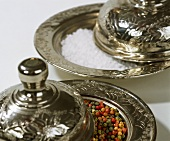Coloured peppercorns and coarse salt on silver platters