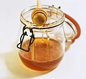 Honigheber auf Einmachglas mit Bienenhonig