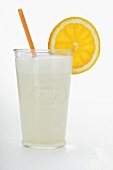 A glass of orange milkshake with straw