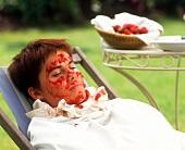 Junge Frau mit Erdbeer-Gesichtsmaske
