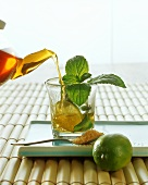 Pouring lime and mint tea into glass