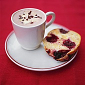 A cup of chocolate and a piece of blackberry muffin