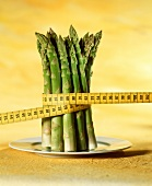 Green asparagus spears with tape measure