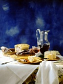 French table scene with sausage, bread, cheese, pâté, wine