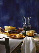 French table scene with sausage, bread, cheese, pate, wine