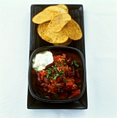 Chili con carne with sour cream and nachos