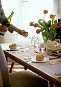 Pouring wine at stylishly laid table with tulips