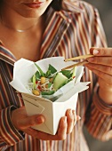 Woman holding take-away container of Asian rice noodle salad