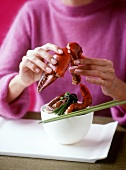 Woman eating crab dish (red-clawed crab)