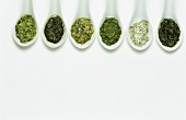 Six different herb sauces on spoons