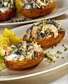 Baked potatoes filled with herring and shrimp salad