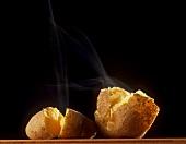Steaming potato, broken open on black background