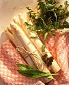 A bundle of asparagus with wild herbs and kitchen cloth