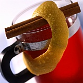 Mulled wine in glass, lemon rind and cinnamon stick