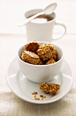 Muesli biscuits in a bowl, cup of coffee behind