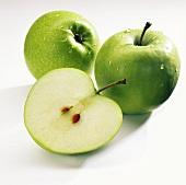 Zwei ganze und ein halber Apfel der Sorte Granny Smith