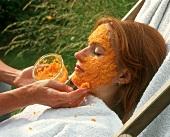 Gesichtsmaske mit Möhren wird bei junger Frau aufgetragen