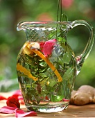Summery herb tea with fresh herbs in glass carafe