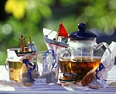 Home-mixed herb tea in tea bags, pot, glass