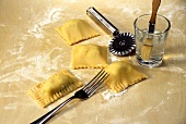 Sealing the edges of ravioli with the prongs of a fork