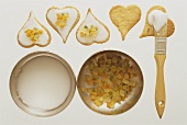Decorating heart-shaped biscuits with glace icing, candied peel