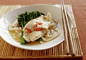 Asian soup with fish, broccoli and udon noodles