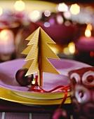 Weihnachtsgedeck mit Papiertannenbäumchen und Kugel