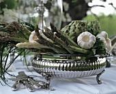 Silver bowl with green asparagus, garlic & artichokes