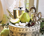 Still life with pears, sugar cubes and silver jugs