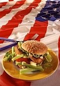 Burger with pork fillet, vegetables & mayonnaise on US flag