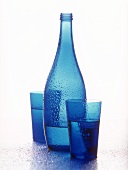 Blue bottle and two blue glasses of mineral water