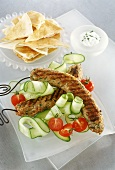 Skewered minced lamb rolls on cucumber slices
