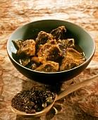 Pork curry (India) spices on wooden spoon in front