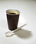 Coffee to go: coffee in plastic cup, plastic spoon