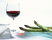 Green asparagus spears and a glass of red wine
