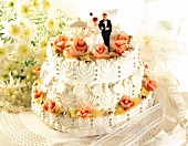 Three-tiered white wedding cake with bride and groom figures