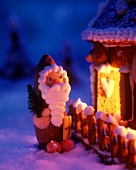 Marzipan Father Christmas in front of a gingerbread house