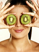 Woman holding two slices of kiwi fruit in front of her eyes