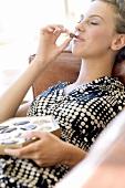 Junge Frau führt geniesserisch eine Praline zum Mund