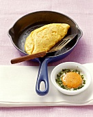 Omelette in a pan and coddled egg in small mould