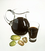 Noni juice in carafe and glass, noni fruits in front