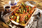 Spicy chicken legs with vegetables in roasting dish