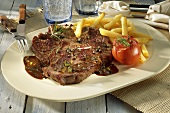 Peppered T-bone steak with chips and baked tomato