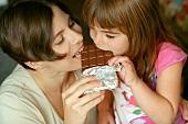 Woman and child biting into same chocolate bar