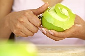 Hands peeling a green apple