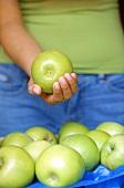 Mensch mit Äpfeln der Sorte Granny Smith