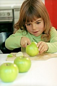 Girl cutting a green apple into pieces (grainy effect)