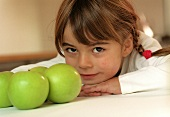 Small girl beside green apples (grainy effect)