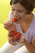 Young woman eating fresh strawberries (grainy effect)