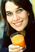Young woman holding glass of carrot juice (grainy effect)